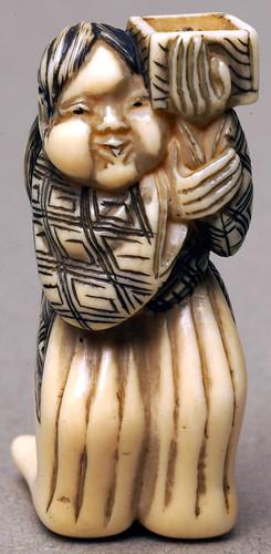 003-Netsuke de Marfil representa a una mujer con el pelo largo recogido hacia atrás con una caja-Bolton Museum and Archive Service