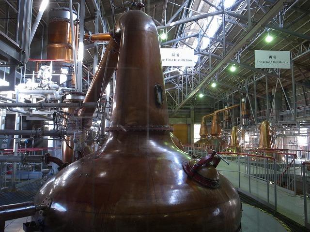 <p>k)蒸留器の棟です。<br /> 精油の蒸留器と同じみたい!<br /> 大きな銅製の蒸留タンクがいっぱい並んでます。</p>