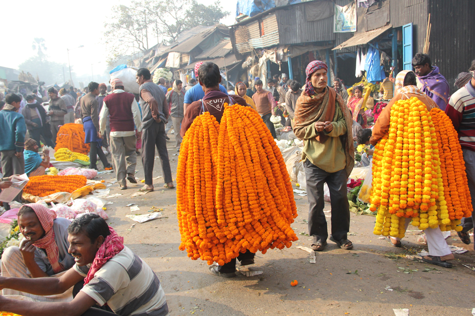 Men walk through the market bearing strands of marigold flowers