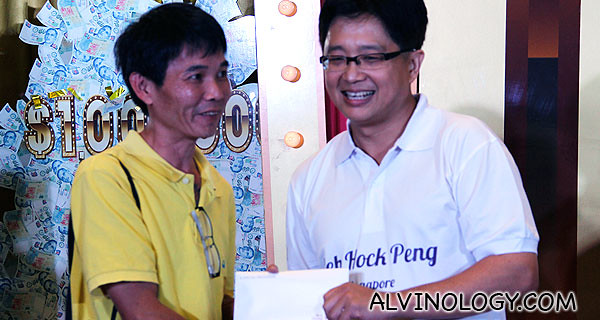 Mr Peh presenting S$500 Changi dollars to a lucky audience who correctly picked Mr Peh as the winner before the show