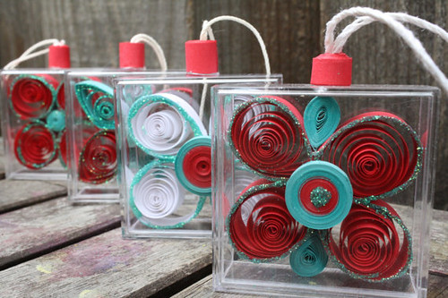 four quilled bento box ornaments made of red, green, and white paper strips