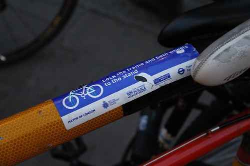 A police sticker on a bike stand shows people how to correctly lock their bike