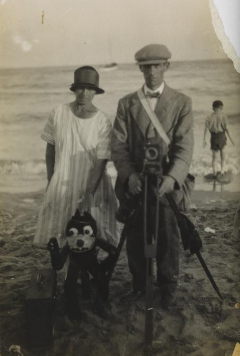Beach photograph of a photographer, woman and Felix the Cat puppet