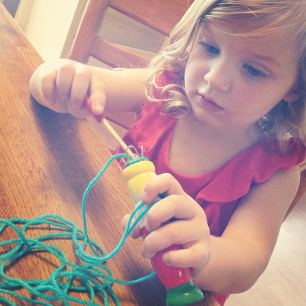 Amelia pretending to use a knitting doll #craft #latergram
