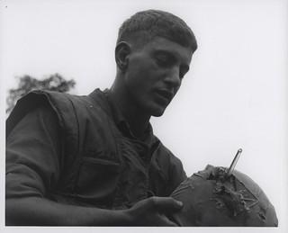 Joseph Luca Examines Hole in His Helmet, 9 March 1967