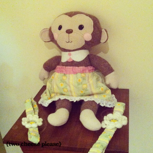 monkey softie sitting on a small table with two headbands
