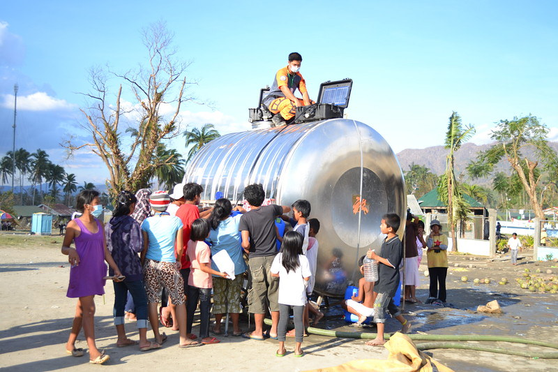 Families queue to get water from tanker after typhoon Bopha by Oxfam International @ flickr