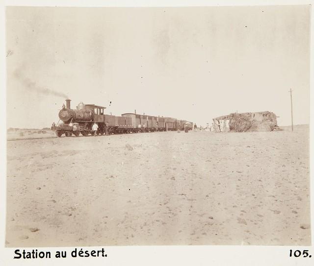Sudan Railways - Baldwin Locomotive Works 4-4-0 steam locomotive and a passenger train at a train station in the desert between Wadi Halfa and Khartoum in 1901