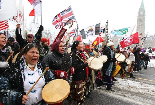 at an Idle No More rally, a group of First Nations protestors hold signs and drums