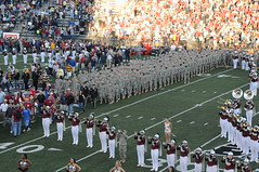 football(0.0), sport venue(1.0), marching band(1.0), musician(1.0), people(1.0), cheering(1.0), musical ensemble(1.0), crowd(1.0), audience(1.0), marching(1.0), gridiron football(1.0), stadium(1.0), arena(1.0),