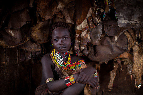 portrait of a girl hamer inside the hut with the backdrop of animal skins