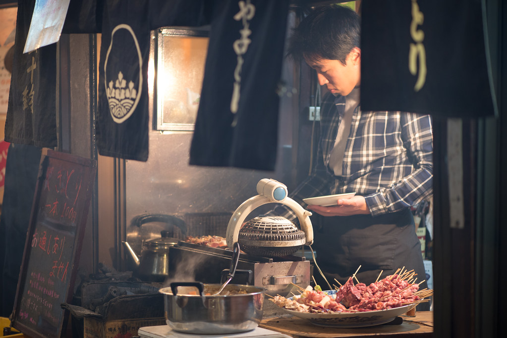 A man stands in front of a little charcoal barbecue turning over Japanese marinated chicken skewers