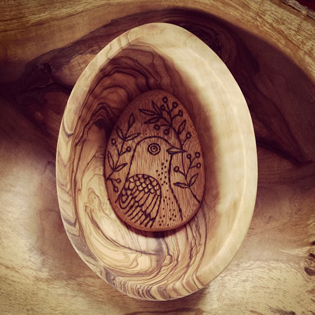 Wood burned bamboo pebble in an egg shaped olive wood bowl.