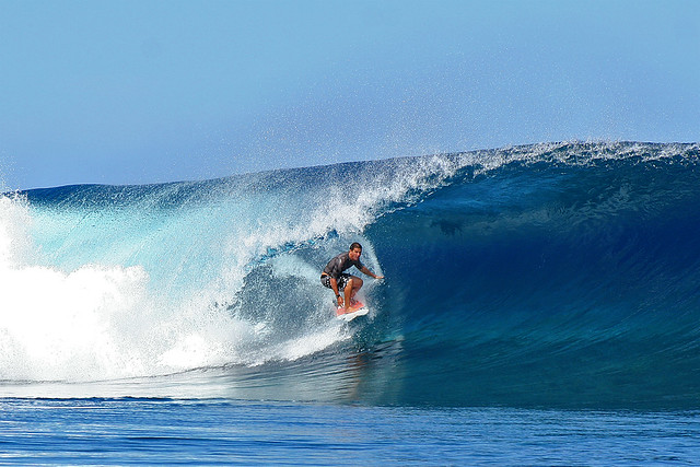 Surfing the waves at Teahupoo, Tahiti.