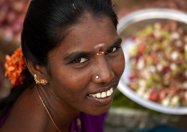 Woman With Bindi, Nose Piercing And Tied Hair With Flowers Smiling At The Camera, Madurai, India