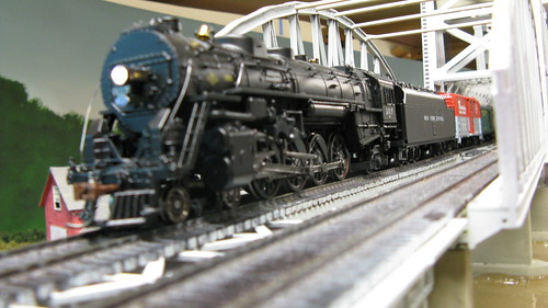 An MTH model of a New York Central 4-8-2 Mohawk class steam locomotive exits the Missisippi River bridge with a passenger train in tow. by Eddie from Chicago