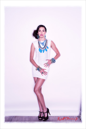 Full length studio shot of female model in white dress wearing chunky blue beaded antique style bracelets teamed with beaded necklaces with feather details and matching earings. Photography by Kent Johnson.