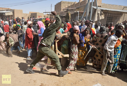 A Malian soldier trys to disperse looters in the streets of Timbuktu on January 29, 2013. by Pan-African News Wire File Photos