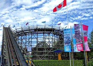 Image of Coaster. woodenrollercoaster playland playlandatthepne pne pacificnationalexhibition rollercoaster wooden classiccoaster aceclassiccoaster rails trestle eastvancouver ride flag banner weather weatherphotography