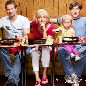 Three members of the Raising Hope family sit on sofas in front of the TV, with TV dinners on trays in front of them. The baby has comandeered the remote control. s