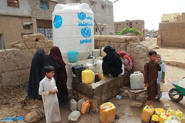 donne e bambini raccolgono l'acqua