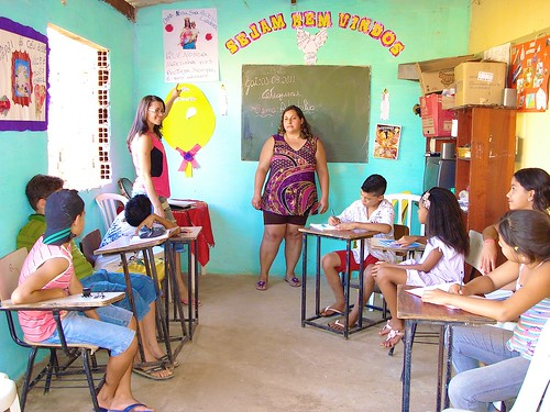 Real Conquista Project, Goiânia, Brazil. A group of catechists and children in the painted and decorated patio during a class