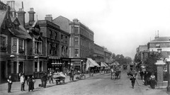 A black-and-white vintage photo showing a view down a wide street with buildings on both sides, all of varying architectural styles. The pavements are busy with pedestrians, and several horse-drawn vehicles are travelling down the road.