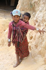 Hill Tribe Girl carrying her sibling in a sling Shan State Myanmar Burma