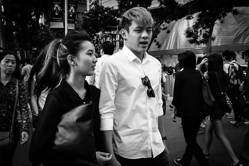 A young couple crossing the busy intersection between Cineleisure and the H&M building