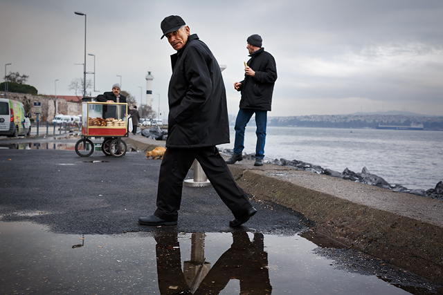 Turkish man stepping over a puddle in Istanbul.