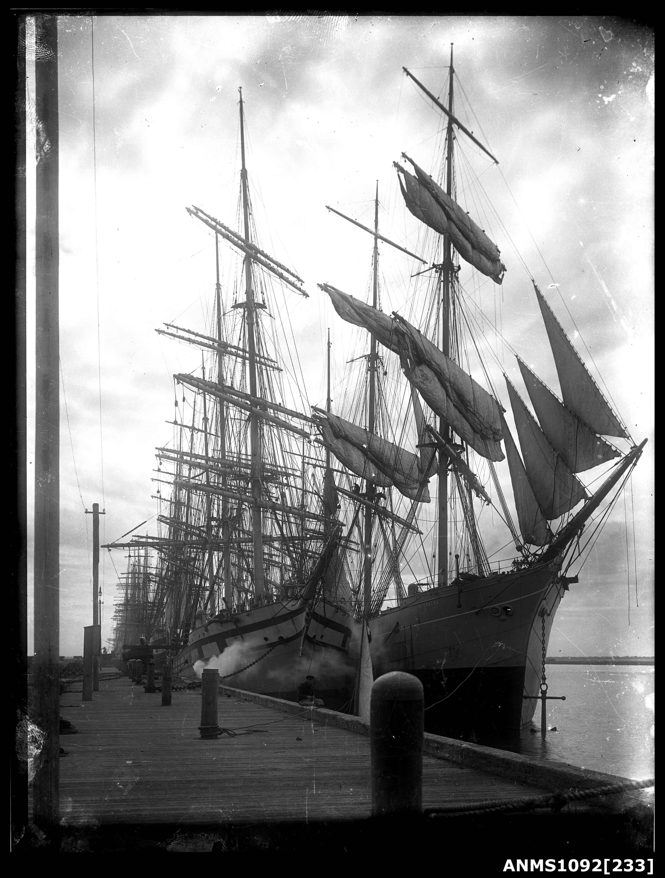 Square rigged sailing ships, including INVERNESS, moored at a wharf