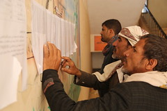 Yemenis look for their names on the food assistance lists.