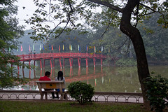 Couple on a Bench in front of The Huc Bridge on Hoan Kiem Lake - Hanoi, Vietnam