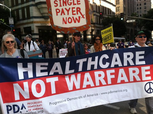 Healthcare advocates march carrying a red white and blue banner reading, Healthcare not Warfare.