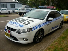 race car(0.0), sports car(0.0), automobile(1.0), automotive exterior(1.0), family car(1.0), vehicle(1.0), police(1.0), police car(1.0), ford fg falcon(1.0), full-size car(1.0), compact car(1.0), bumper(1.0), sedan(1.0), ford falcon (australian version)(1.0), land vehicle(1.0), luxury vehicle(1.0),
