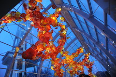 Orange and yellow sculpture with the base of the Space Needle, Dale Chihuly's Glass and Garden, Seattle Center, Washington, USA