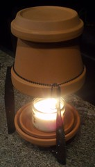 A ceramic flower pot made of terra cotta heated by a jar candle to create a space heater