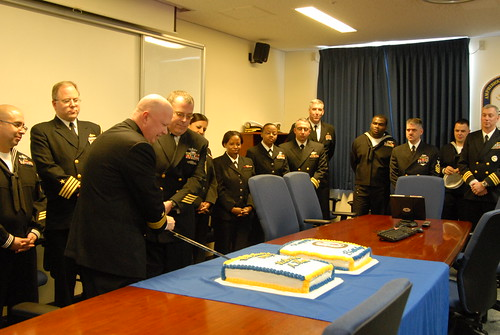 Rear Adm. Jeffrey Harley, commander of ESG 7, cuts a cake with Master Chief Operations Specialist Michael Bauman