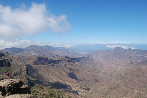 Auf einem überhängenden Felsen werden Wanderer abgelichtet, im Hintergrund der Teide