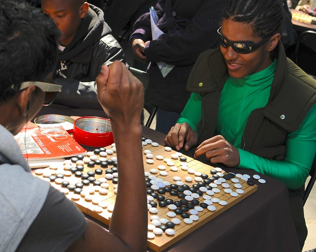 Visitors play the game of go with the Brooklyn Go Club at Puzzle Plaza. Photo by Mike Ratliff.