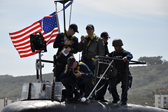 Cmdr. Douglas Bradley, commanding officer of USS Asheville (SSN 758) and crew members stand on the conning tower as the boat departs for deployment, March 26. (U.S. Navy photo by Mass Communication Specialist 2nd Class Kyle Carlstrom)