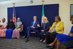 U.S. Secretary of State John Kerry, joined by Assistant Secretary of State for African Affairs Linda Thomas-Greenfield, listens as U.S. Ambassador-at-Large for Global Women's Issues Catherine Russell addresses a group of young women who have been empowered, or are encouraging others to be empowered, through women's education on August 24, 2016, in the Rosa Parks Room at the U.S. Embassy in Abuja, Nigeria. [State Department Photo/ Public Domain]
