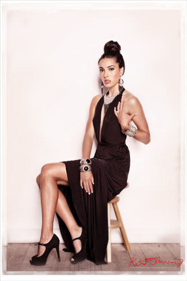 Full length seated fashion portrait for a jewellery campaign, model wears black evening dress with black beaded necklace, braclets and matching earings. Photography by Kent Johnson, Sydney, Australia.