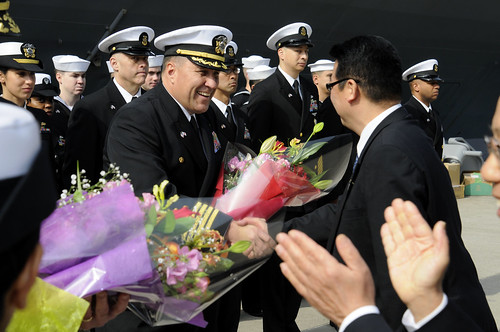 USS Blue Ridge (LCC 19) Commanding Officer Capt. Will Pennington greets Japanese officials during a welcoming ceremony.