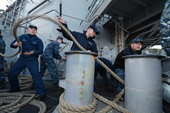 Sailors heave a line on the fantail as amphibious assault ship USS Bonhomme Richard (LHD 6) departs Sasebo, Japan, Jan. 24. (U.S. Navy photo by Mass Communication Specialist 2nd Class Betsy Knapper)