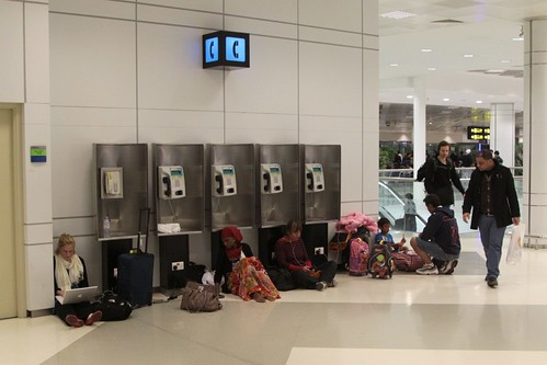 Passengers sit on the departure terminal floor, seeking out power outlets