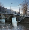 Crossing the steep and snowy bridge in the heart of Amsterdam