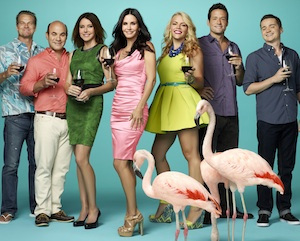 The cast of Cougar Town holding glasses of red wine.