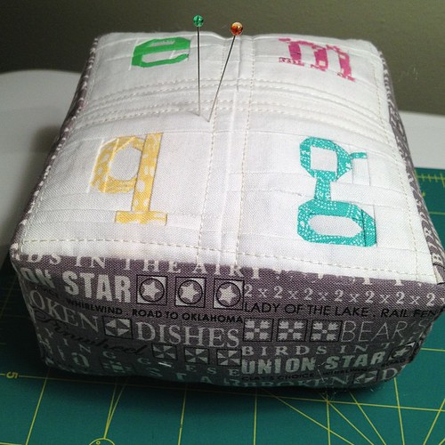 "Pincushion, about 5"" square, 2.5"" high. Letters are 1-1.5"" square from pattern by @quietplay reduced by 50%. Tomorrow I will finish the stuffing and take daytime pictures."