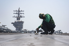 Sailor conducts maintenance on a bow catapult on the flight deck of USS Dwight D. Eisenhower.